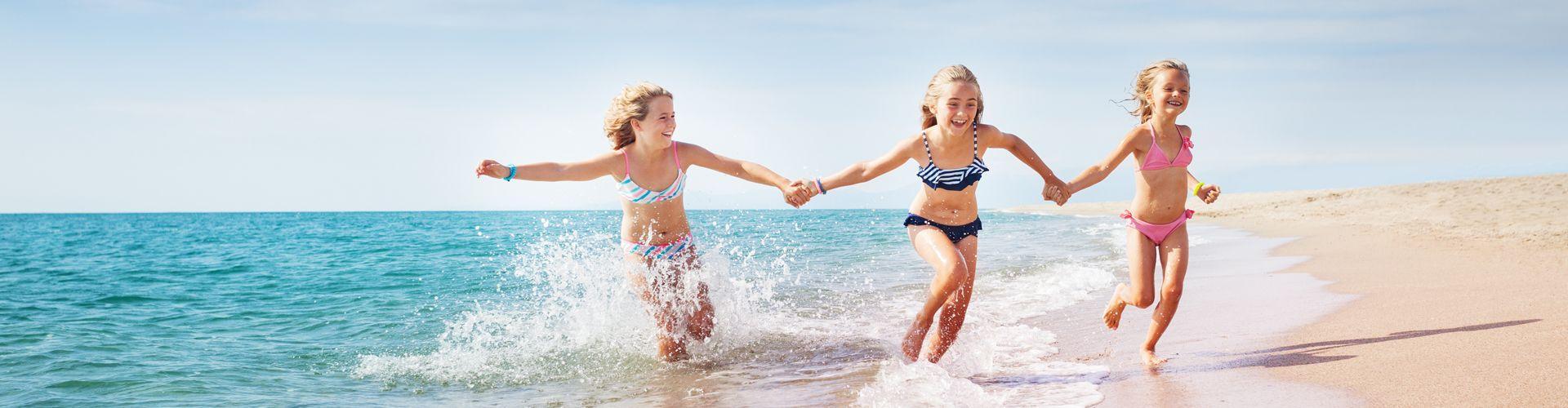 Roześmiane dzieci biegnące po plaży